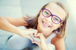girl with purple glasses and braces making heart with hands